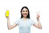 KYIV, UKRAINE - JULY 15, 2019: happy brunette asian woman holding smartphone with snapchat app and showing peace sign isolated on white