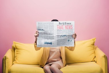 Asian woman holding newspaper with fake news in front of face while sitting on yellow sofa isolated on pink stock vector