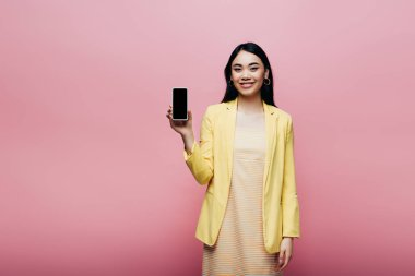 Happy asian woman in yellow outfit holding smartphone with blank screen isolated on pink stock vector