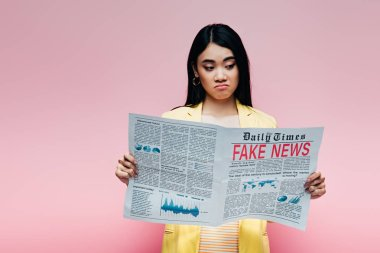 Upset asian woman in yellow outfit reading newspaper with fake news isolated on pink stock vector