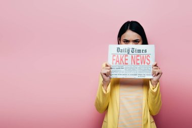 Sad asian woman in yellow outfit holding newspaper with fake news isolated on pink stock vector