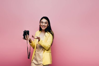 Happy asian woman in yellow outfit holding digital camera isolated on pink stock vector