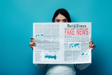 Asian woman in white blouse holding newspaper with fake news on blue background stock vector