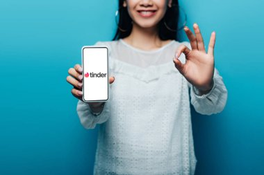 KYIV, UKRAINE - JULY 15, 2019: cropped view of smiling asian woman in white blouse showing ok sign and smartphone with tinder app on blue background stock vector