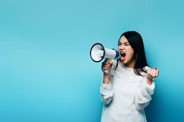 Angry brunette asian woman screaming in loudspeaker on blue background stock vector