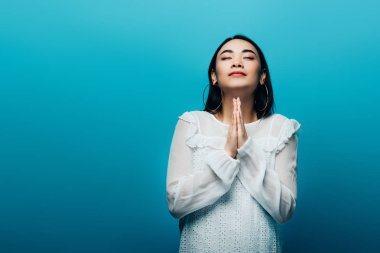 Brunette asian woman with closed eyes and praying hands on blue background stock vector
