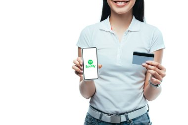 KYIV, UKRAINE - JULY 15, 2019: cropped view of smiling brunette asian girl holding credit card and smartphone with spotify app isolated on white stock vector