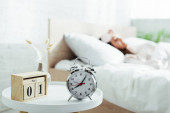 selective focus of alarm clock and calendar in bedroom at morning