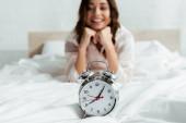 selektivní zaměření atraktivní ženy při pohledu na budík ráno