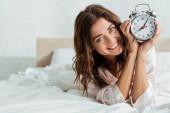 atraktivní žena s úsměvem a držení budíku na ráno