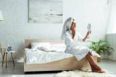 atraktivní žena v županu a ručník při pohledu na zrcadlo ráno