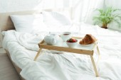 Photo wooden tray with teapot, up, croissant and strawberries at morning