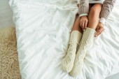 cropped view of woman taking on knitted socks at morning