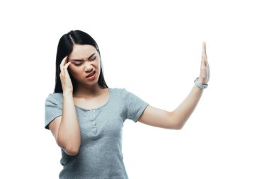 attractive asian girl suffering from headache and showing stop gesture isolated on white