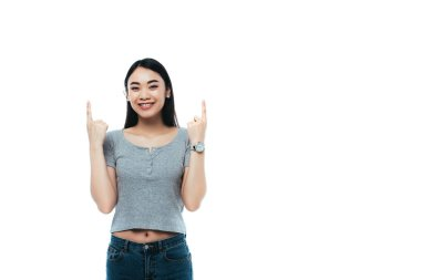 Happy asian girl pointing with fingers upwards isolated on white stock vector