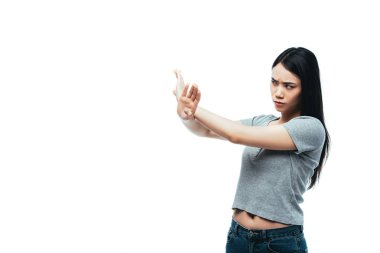 displeased asian girl showing stop gesture isolated on white