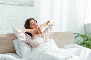 attractive woman with closed eyes stretching herself at morning