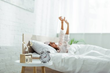 Selective focus of alarm clock and calendar in bedroom at morning stock vector