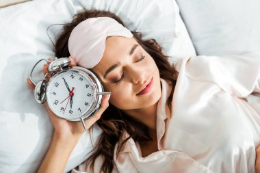 Top view of attractive woman with sleeping mask holding alarm clock at morning stock vector