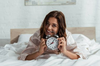 Attractive woman smiling and holding alarm clock at morning stock vector