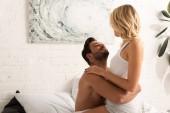 Fotografie beautiful girlfriend and boyfriend hugging in bed in the morning