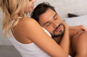 šťastný něžný muž a žena objímání v posteli ráno