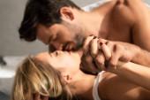 selektivní zaměření smyslného páru objímání, líbání a držení se za ruce v posteli ráno