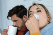 sick man with hot drink and woman with napkin having runny nose