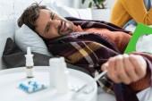 nemocný muž v posteli s prášky, ubrousky a nosní sprej v ložnici se ženou