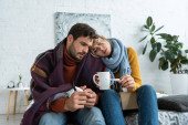 ill couple holding thermometer, hot drink and nasal spray in bedroom