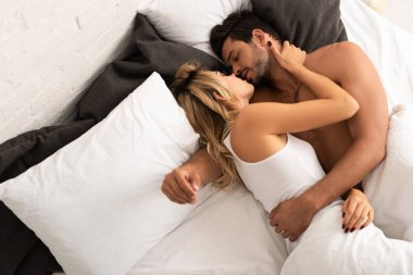 happy tender couple kissing and hugging in bed in the morning