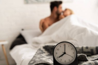 Selective focus of alarm clock amd tender couple kissing in bed in the morning stock vector