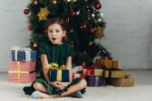 překvapené dítě sedí na podlaze u vánočního stromku, drží dárkovou krabici a dívá se do kamery