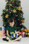 rozkošné dítě sedí na podlaze v blízkosti vánočního stromku a drží dárkové krabice