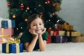 glückliches Kind liegt auf dem Boden neben Geschenkbox und lächelt in die Kamera
