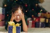 Lächelndes Kind liegt auf dem Boden in der Nähe von Geschenkschachteln und bedeckt die Augen mit Händen