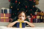 Fotografie verträumtes Kind schaut weg, während es in der Nähe von Geschenkschachtel und Weihnachtsbaum auf dem Boden liegt