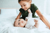 smiling child looking at adorable infant lying on white bedding