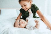 Fotografie smiling child looking at adorable infant lying on white bedding