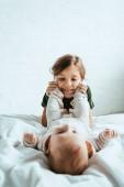 Fényképek szelektív fókusz boldog gyermek megható lábak imádnivaló baba fekvő fehér ágynemű