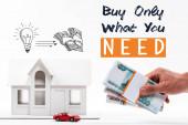 Fotografie abgeschnittene Ansicht eines Mannes mit Geld in der Nähe von Haus- und Automodellen, kaufen Sie nur das, was Sie brauchen Schriftzug isoliert auf weiß