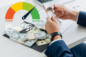 cropped view of businessman counting money in office with credit score illustration