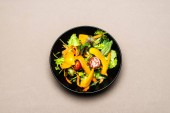 top view of healthy salad in black plate on table