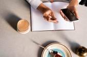 részleges kilátás nő jegyzetfüzet segítségével smartphone kávézó tortával és kávéval