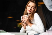 dreamy woman with closed eyes holding cup of coffee in cafe