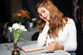 Fotografie attractive tender woman reading book in cafe with cup of coffee and smartphone