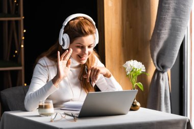 beautiful happy woman in headphones waving and having video chat on laptop in cafe