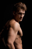 handsome shirtless man posing isolated on black
