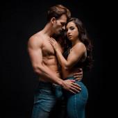 junges sinnliches Paar umarmt, isoliert auf schwarz