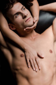 young woman hugging sexy man on sofa in dark room
